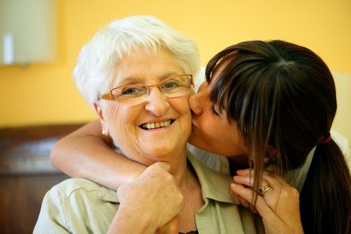 Young woman kissing her elderly mother on the cheek while both are smiling.